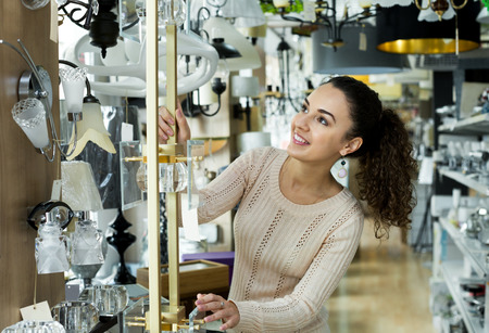 bright housekeeping: Attractive young female customer buying interior lights for home in mall