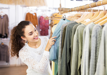 25 35: Pretty young brunette choosing new skirt on hangers in shop Stock Photo