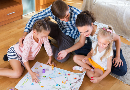 mother board: Happy young family of four playing at board game in domestic interior