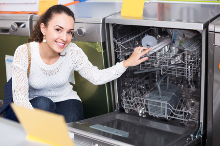 domestic appliances: Average female customer choosing at dishwashers in domestic appliances store Stock Photo