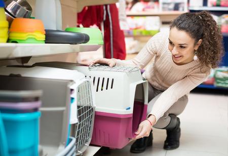 petshop: Portrait of young woman purchasing pet kennels in petshop Stock Photo