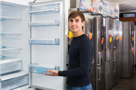 domestic appliances: Young man choosing new refrigerator in domestic appliances store
