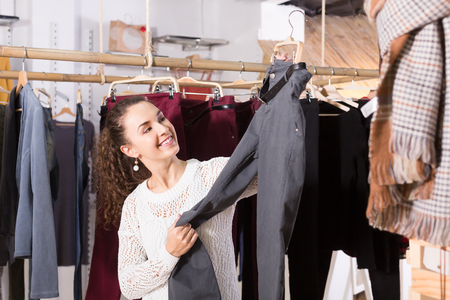 clothing store: Young female brunette choosing trousers and smiling