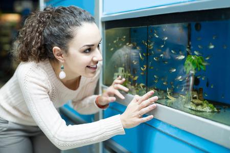 fish tank: happy spanish female customer watching tropical fish in aquarium tank
