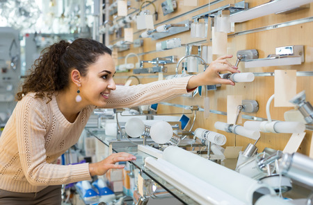 bright housekeeping: smiling  young american  woman doing shopping in lighting shop