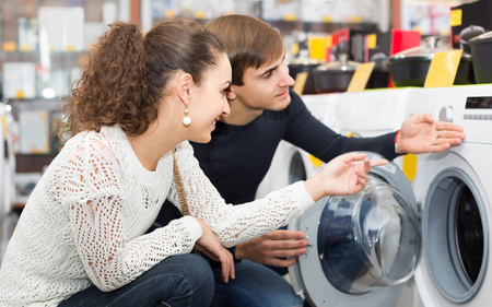 front loader: happy european couple choosing washing machine in hypermarket and smiling