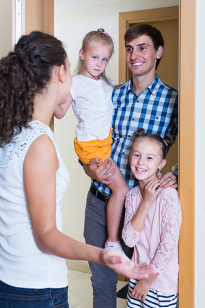 recieving: smiling adults and kids meeting at doorway and greeting one another