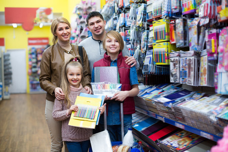 writing materials: Parents with kids selecting writing materials in mall