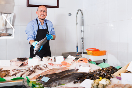 Positive smiling mature salesman with apron offering fresh fish in shop