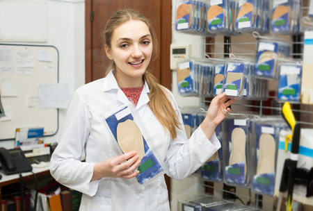 orthopaedic: Young american professional physician offering orthopaedic insoles in special shop Stock Photo