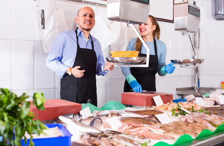 fishery: girl and salesman posing near display with chilled fish at fishery Stock Photo