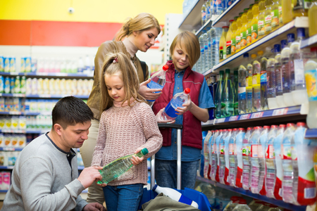 sparkling water: Parents with two children purchasing bottle of sparkling water in supermarket. Selective focus