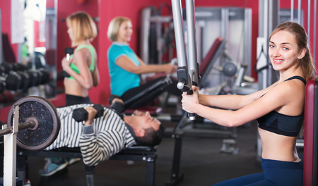 satisfied people: Positive glad satisfied people  weightlifting training in modern health club
