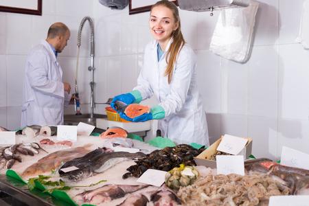 shopgirl: Joyful smiling shopgirl and salesman near display with cooled fish Stock Photo
