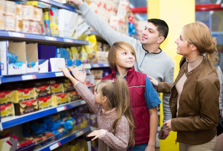 12 class: positive american parents with two kids choosing crispy flakes in shop