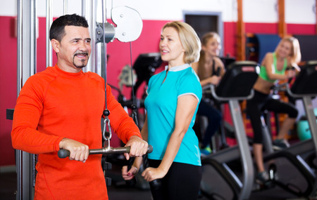 strength training: Smiling people of different age having strength training in gym