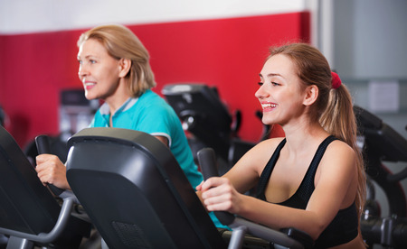 age 60: Smiling elderly and young women working out in gym for female