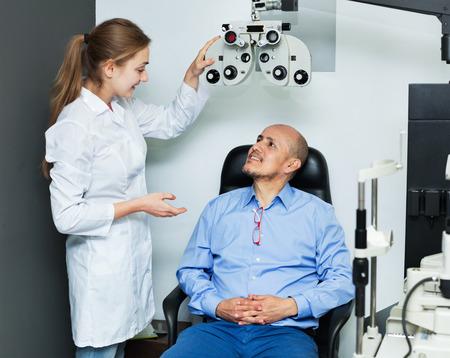 55 60: Female optician doing eye examination with aid of slit lamp Stock Photo