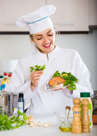 jorobado: Positive female chef posing with trout fillet in kitchen