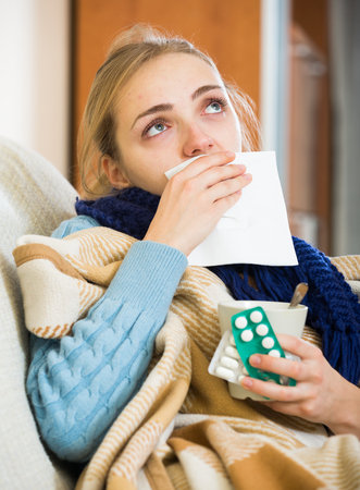 megrim: Young woman with cold and blocked nose at home