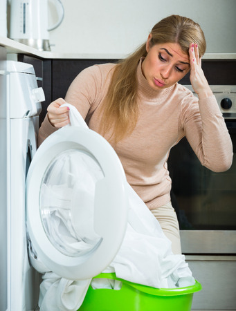 charwoman: Adult woman displeased with washing quality of linen after laundry at home
