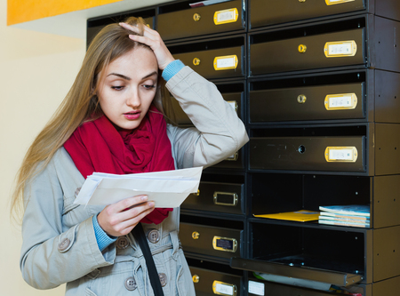the ugly: Young upset woman in coat receiving ugly news by post Stock Photo