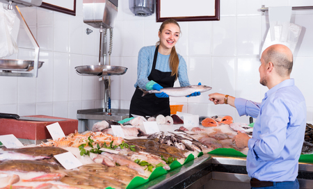 shopgirl: Friendly shopgirl offering fresh fish and chilled seafood to client