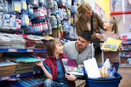 Parents with children choosing writing materials in mall