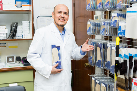 insoles: Mature orthopedist standing near assortment of insoles in orthopaedic store