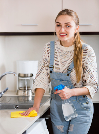 householder: Portrait of positive housewife cleaning with supplies in kitchen Stock Photo