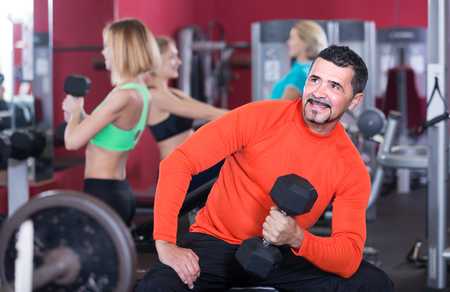 anaerobic: Several positive women and man having powerlifting training on machines in gym Stock Photo