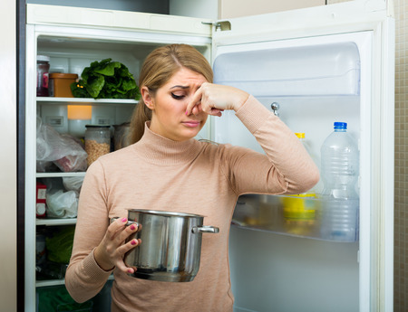 loathsome: Upset young housewife holding pot with foul meal near fridge in home kitchen