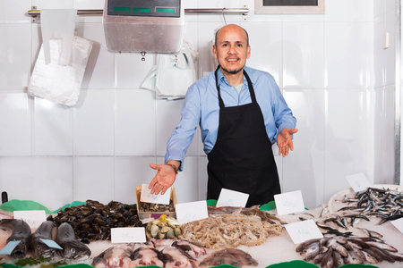 45 50: Positive mature salesman with apron offering fresh fish in shop Stock Photo