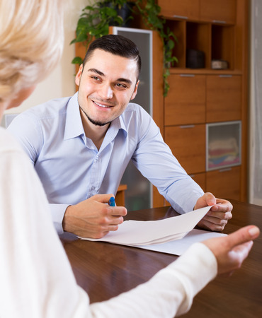 mismatch: Smiling handsome man and aged woman sitting with banking documents indoors