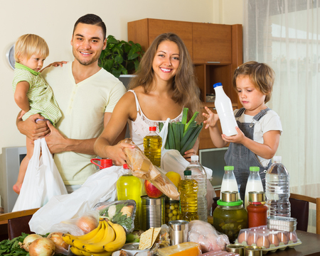 purchased: Young smiling family with little children sorting purchased food out indoor Stock Photo