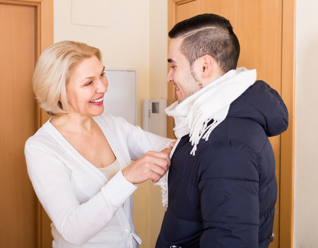 woman mature: Smiling senior woman seeing off young boyfriend at doorway