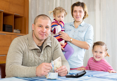 30 35: Happy parents with daughters counting money after salary. Focus on man Stock Photo