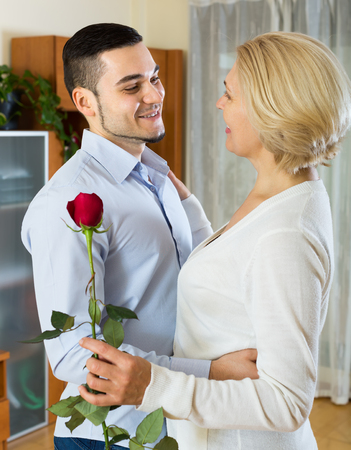 mismatch: Young handsome man and senior woman slowly dancing and smiling indoor