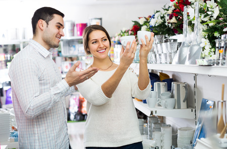 ware: Smiling adult couple buying ceramic ware in the shop Stock Photo