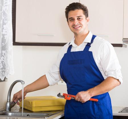 unblock: Happy specialist in uniform fixing leak at house Stock Photo