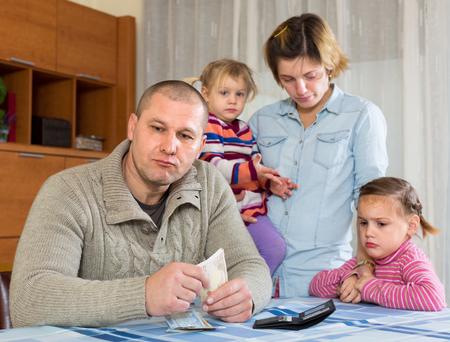 Les problèmes financiers en famille. Malheureuse avec des enfants contre mari à la maison avec de l'argent Banque d'images - 53494398