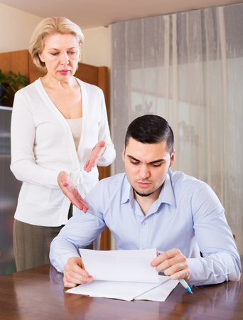 mismatch: Elderly woman questioning young man about letters from bank Stock Photo