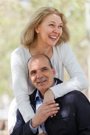 heterosexual: Happy aged heterosexual couple with smiles holding hands of each other outdoor