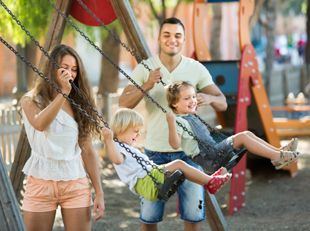 Smiling young family of four at playgrounds swings. Focus on woman