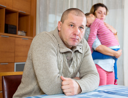 insult: Family quarrel. Sad man against unhappy young woman at home Stock Photo