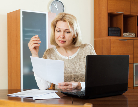 ruminate: Serious woman staring financial documents with laptop  at table in home