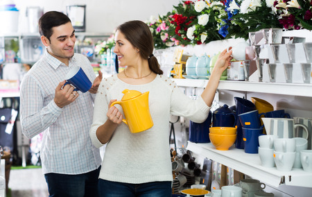 25 35: Positive young couple buying ceramic ware in the shop