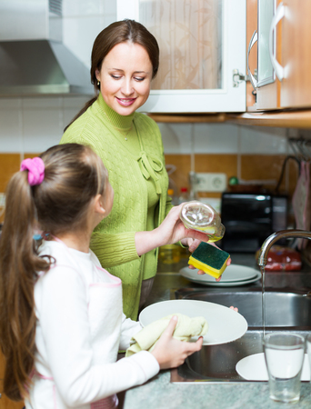 9 10 years: Daughter helping mother washing dishes in the kitchen
