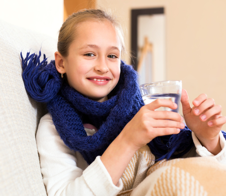 7 8 years: Ill girl on a couch under the blanket with a warm drink Stock Photo