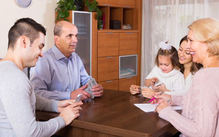 grand child: Long happy family with grand children sitting at table with cards Stock Photo